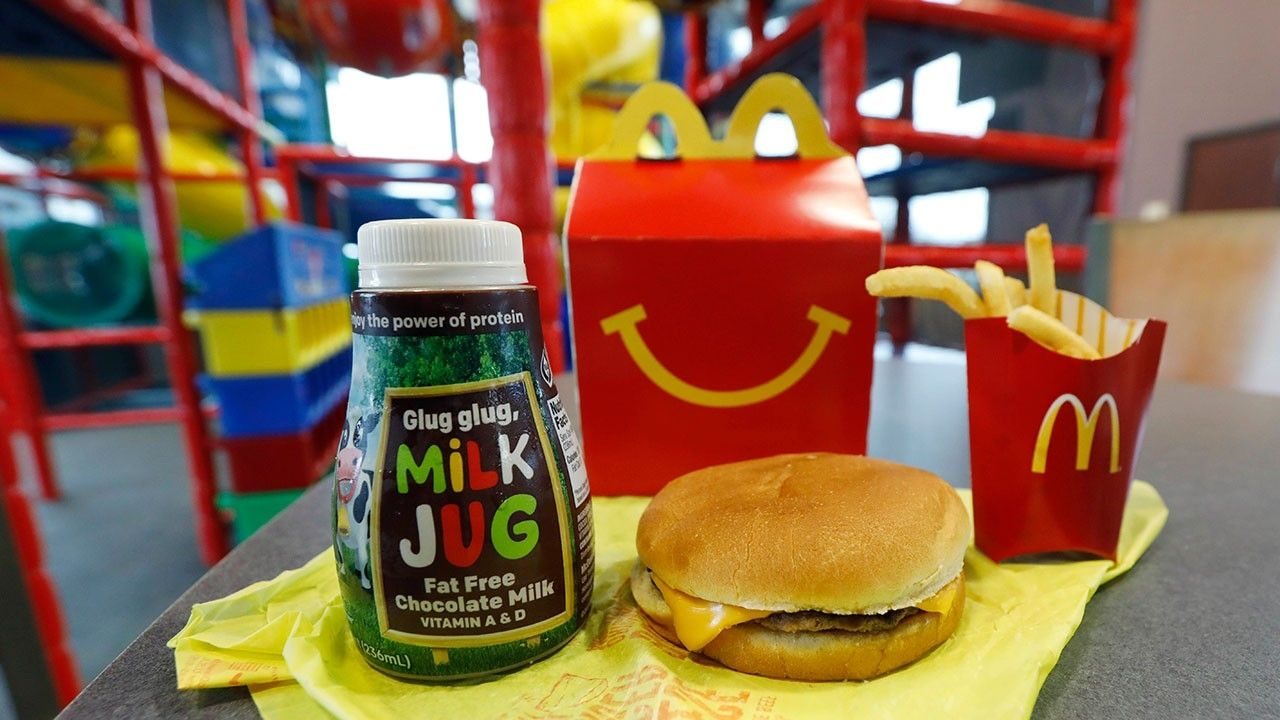 """McDonald's is tweaking its beloved Happy Meal once again. On Thursday, McDonald's announced plans to remove excess calories, sodium and saturated fat from its Happy Meal offerings, largely by reformulating or removing certain Happy Meal staples — namely cheeseburgers and chocolate milk — from the menu. As part of its new initiative to """"offer more …"""