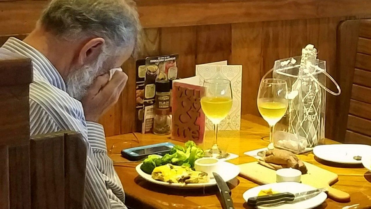 """The unidentified man is neatly dress and appears to be crying into a folded napkin. There are two place settings on the table and two glasses of wine. There also appeared to be a Valentine's Day card on the table that reads """"You & Me."""" Chasidy Gwaltney, of Corpus Christi, shared the photo on Facebook. …"""